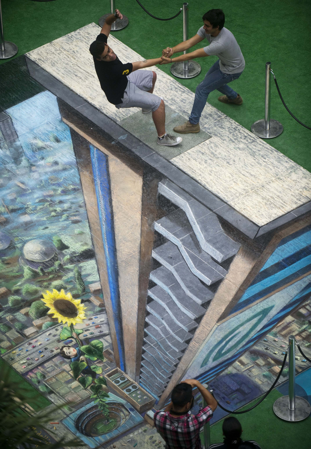 Two men pose by the work of British artist Julian Beever, specialized in pavement drawings, wall murals and realistic paintings, made in a shopping center in Medellin, Antioquia department, Colombia on September 5, 2013. Beever made the painting using colour chalks. AFP PHOTO /Raul ARBOLEDA